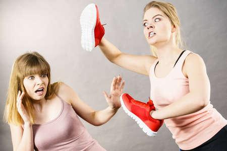 Agressive women having argue fight using shoes, female friend being scared. Violance concept. Banque d'images