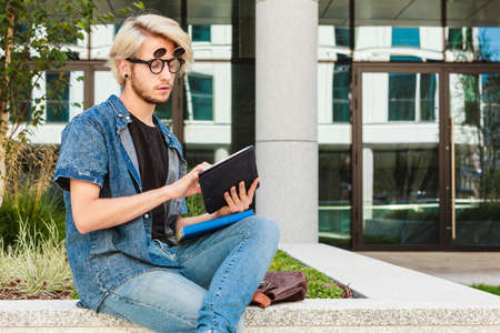 Male fashion, technology, student concept. Guy with tablet wearing jeans outfit and eccentric sunglasses sitting on white ledge