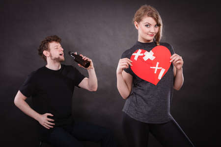 Family and alcoholism problems. Addiction and trouble of drinking. Man with alcohol bottle. Woman holds paper broken heart smiling because make right decision  Stock Photo