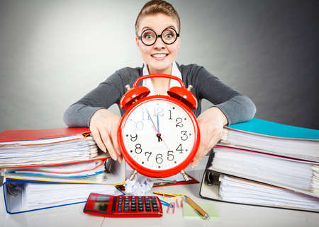 Paper work against time. Young expressive woman in office with big red clock. Crazy happy businesswoman close to ending her work. Stock Photo