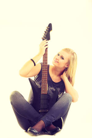 Love to music. Young pretty girl with black electric guitar. Blonde woman with passion to playing. Female musician holds instrument. Stock Photo