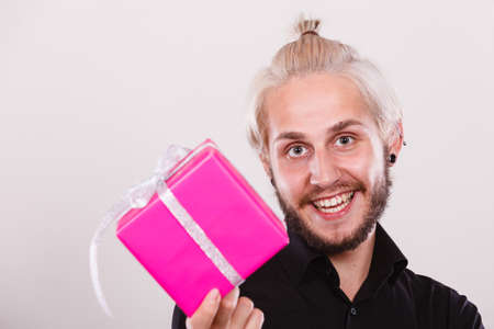 People celebrating xmas, love and happiness concept - cool young man holding present pink gift box in hand