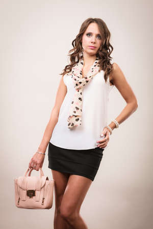 Elegant outfit. Female fashion. Girl in fashionable clothes holding bag handbag studio shot on gray background Stock Photo