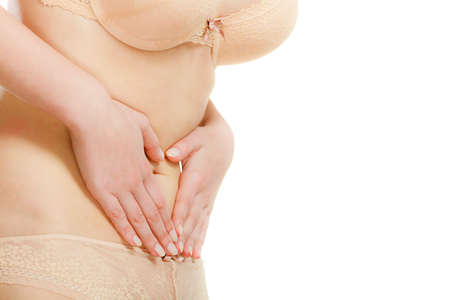 Bellyache or menstruation. Syndroms of indigestion pregnancy. Closeup woman wearing lingerie suffering from stomach pain isolated on white