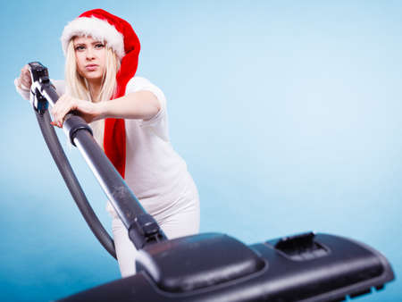 Woman vacuuming the house, Teen girl in santa helper hat with vacuum cleaner, funny face expression. Christmas time, last minute housework concept. Stock Photo