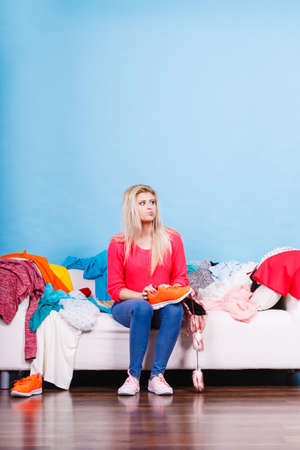Clothing dilemmas concept. Woman does not know what to wear sitting on messy couch with piles of clothes. Stok Fotoğraf