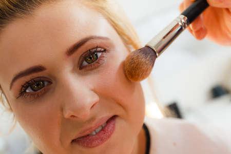 Visage, beauty concept. Closeup portrait of woman face getting her face makeup done by professional artist brush to apply powder Foto de archivo