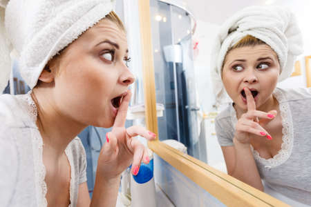 Woman looking at her reflection in mirror thinking about her complexes, analyzing face skin complexion showing silence gesture with finger close to mouth