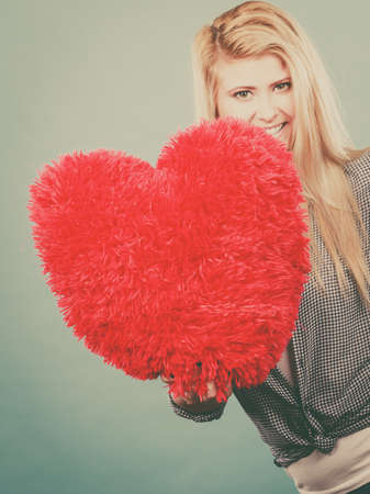Love, romance, valentines day gift idea concept. Happy woman holding big red fluffy pillow in heart shape Stock Photo