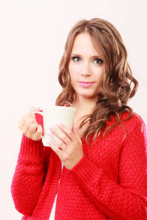 Attractive fall girl long hair red autumnal sweater holding white mug with coffee warm beverage. Woman warming herself 스톡 콘텐츠