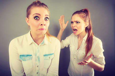 Conflict, bad relationships, friendship difficulties. Two young women having argument. Angry fury girl screaming at her friend or younger sister Stock Photo