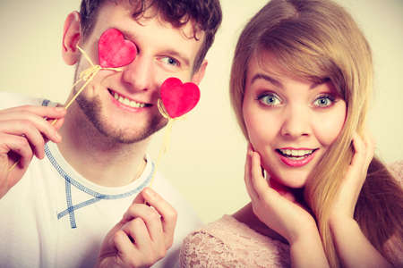 Love and happiness concept. Cheerful enjoyable young couple with little small hearts on sticks covering woman man eyes. Lovers blinded by their big love. Stock Photo
