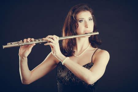 Musique et élégance. Séduisante femme élégante jouant sur la flûte traversière. musicien Femme avec son instrument performant.