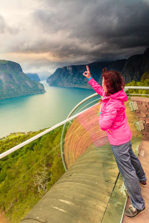 Tourist woman on Stegastein viewpoint enjoying Aurland fjord view making victory gesture sign, Sogn Og Fjordane, Norway
