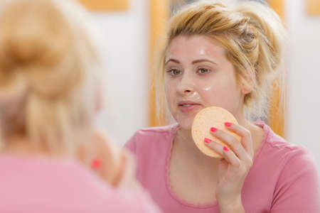 Complexion, skincare products concept. Woman having wash gel on face holding sponge about to clean her skin. Stock Photo
