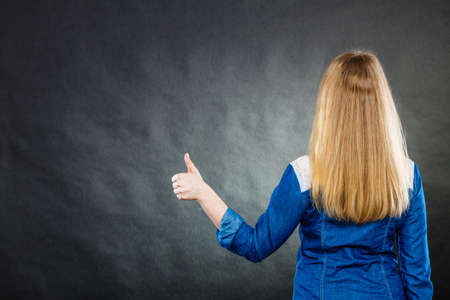Positiveness and success concept. Back view of blonde woman with long straight hair. Girl showing thumb up gesture. Body expression.