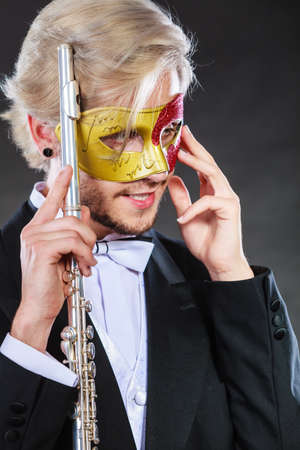 Holidays, people and celebration concept. Elegant young guy wearing suit white shirt bow tie and carnival venetian mask holding flute instrument on dark