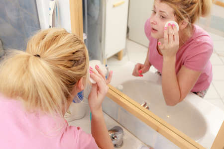 Skin complexion care concept. Young woman using cotton pad to remove make up or dirt from face. Stock Photo