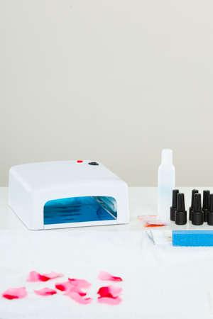 Manicure ibrido professionale gel con lampada UV portata al salone di estetista. Concetto di oggetti di trattamento termale benessere benessere Archivio Fotografico - 92550817