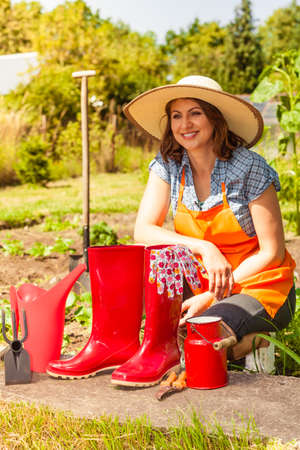 Gardening tools outdoor in garden, red rubber boots and water can. Woman farmer in hat in the background Stock Photo
