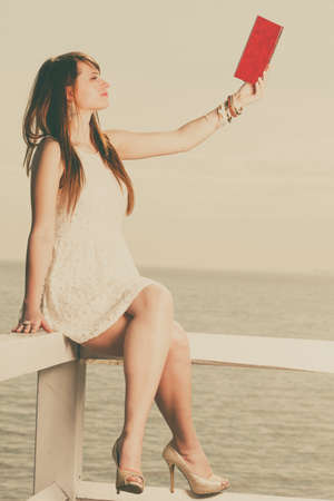 Books, bookworm, travel, leisure time concept. Beautiful woman wearing white dress sitting on wooden hurdle near sea and book in the air