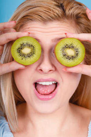 Healthy diet, refreshing food full of vitamins. Woman holding sweet delicious green kiwi fruit, pretending it is eyeglasses. Stock Photo