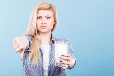 Lactose intolerance, health problem with dairy food products concept. Woman holding glass of milk showing thumb down gesture.