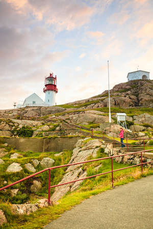 Tourist woman and historic red white lighthouse on the edge of rocky sea coast, South Norway, Lindesnes Fyr beacon