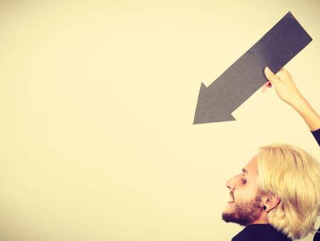 Planificación, direcciones, concepto de las opciones. Hombre que sostiene la flecha que apunta hacia la izquierda por negro. tiro de interior sobre fondo claro Foto de archivo - 93219304