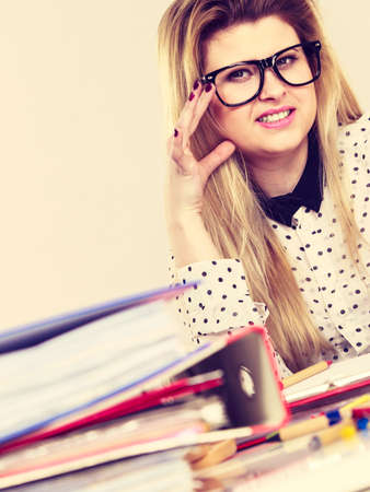 Happy business woman feeling energetic sitting working at desk full off documents in binders. Stock Photo