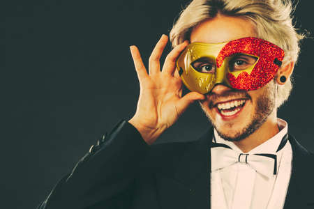Valentines day. Love concept. Holidays and celebration. Elegant young guy wearing suit white shirt bow tie with carnival mask and heart stick in hand, on dark. Stock Photo
