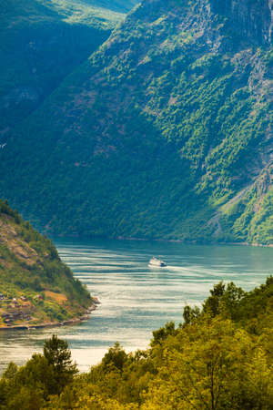Tourism vacation and travel. Mountains landscape and ship ferry boat on Geirangerfjord fjord in Norway Scandinavia.