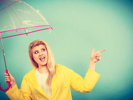 Blonde woman wearing yellow raincoat holding transparent umbrella checking weather if it is raining pointing with finger at copyspace. Stock fotó - 93539431