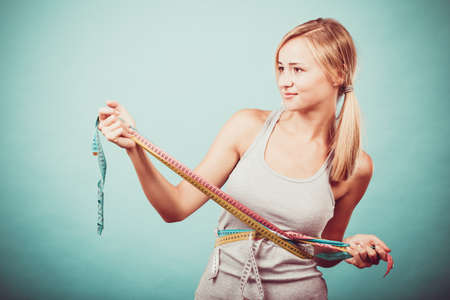 Weight loss, slim body, healthy lifestyle concept. Fit fitness girl measuring her waistline body with many colorful measure tapes on blue