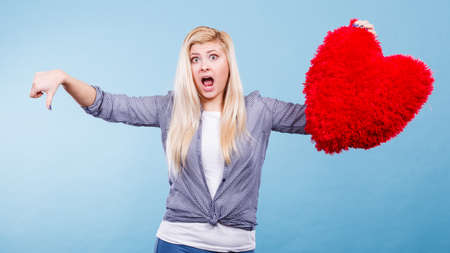 Bad relationship, independence concept. Woman holding big red fluffy pillow in heart shape showing thumb down gesture.