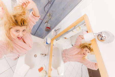 Woman looking at her very tangled blonde dry and damaged hair. Haircare problems concept, wide angle view Stock Photo