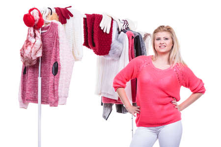Young woman indecision in wardrobe home closet, teen blonde girl choosing her warm fashion outfit on clothing rack. Picking winter autumn clothes, shopping concept. Stock Photo