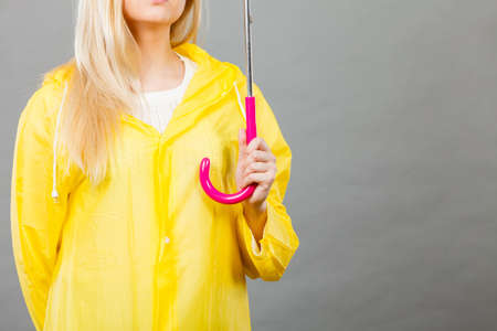 Rainy day autumnal accessories concept. Woman wearing yellow raincoat holding open umbrella. Studio shot on dark background.