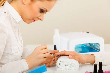 Closeup of beautician painting nails of female client. Woman in beauty spa salon doing manicure Banque d'images