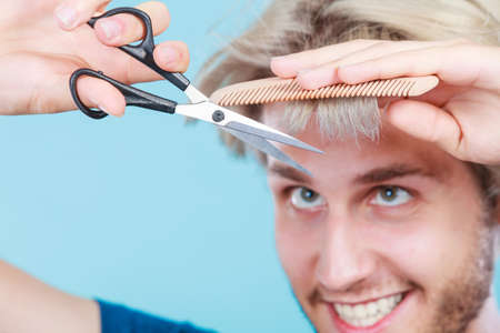 Style and fashion. Young trendy male hairstylist barber with new idea of look changing. Blonde guy with scissors and comb creating coiffure cutting his bangs. Foto de archivo