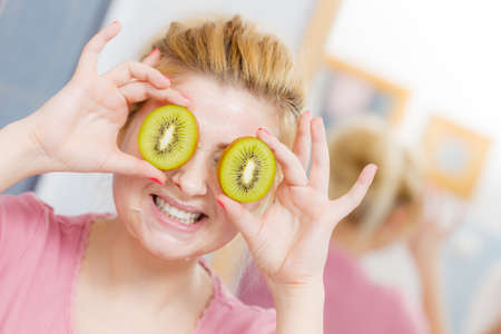 Facial skin and body care, vitamins good complexion treatment at home concept. Young woman having gel peel off mask on her face holding kiwi fruit.