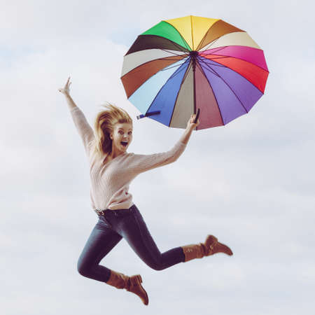 Happiness, enjoying autumn weather, feeling great concept. Woman jumping with colorful umbrella on clear blue sky Stock Photo