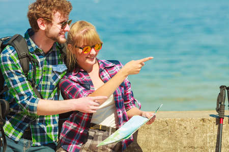Adventure, summer, tourism active lifestyle. Young couple backpacker looking at map by seaside, plan their sightseeing Stock Photo