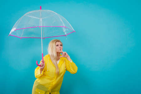 Blonde woman wearing yellow raincoat holding transparent umbrella checking weather if it is raining showing silence gesture. Stock fotó
