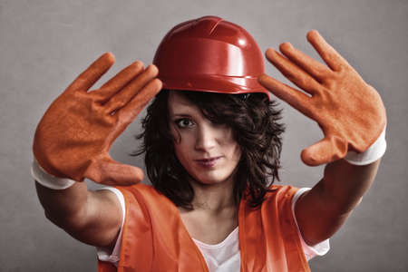 Sex equality and feminism. Sexy girl construction worker builder in orange vest and hard hat showing stop sign hand gesture. Stock Photo