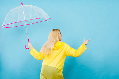 Blonde woman wearing yellow raincoat holding transparent umbrella checking weather if it is raining pointing with finger at copyspace. Stock fotó