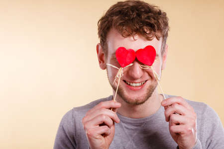 Love romance concept. Man blinded by love. Young male holding hearts on sticks before his eyes.  Stock Photo