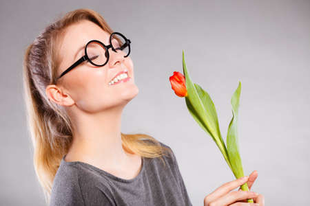 Nature flora beauty concept. Smiling lady sniffing flower. Gorgeous blonde woman in glasses enjoying smell of red tulip.
