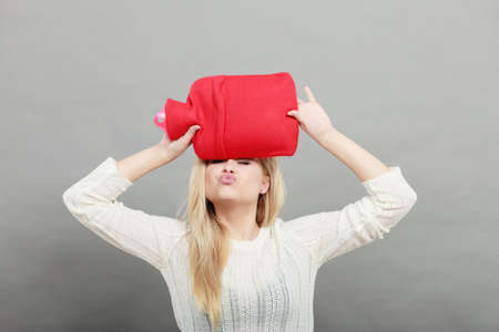 Woman holding red hot water bottle on head to deal with headache Stock Photo