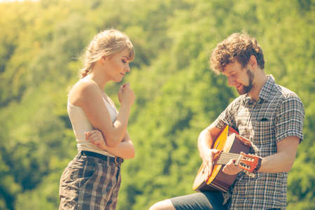 Adventure, tourism, enjoying summer time together - young couple tourists having fun playing guitar in camping
